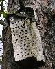Insektenhotel aus einem alten Stück Holz mit kleinem Blechdach